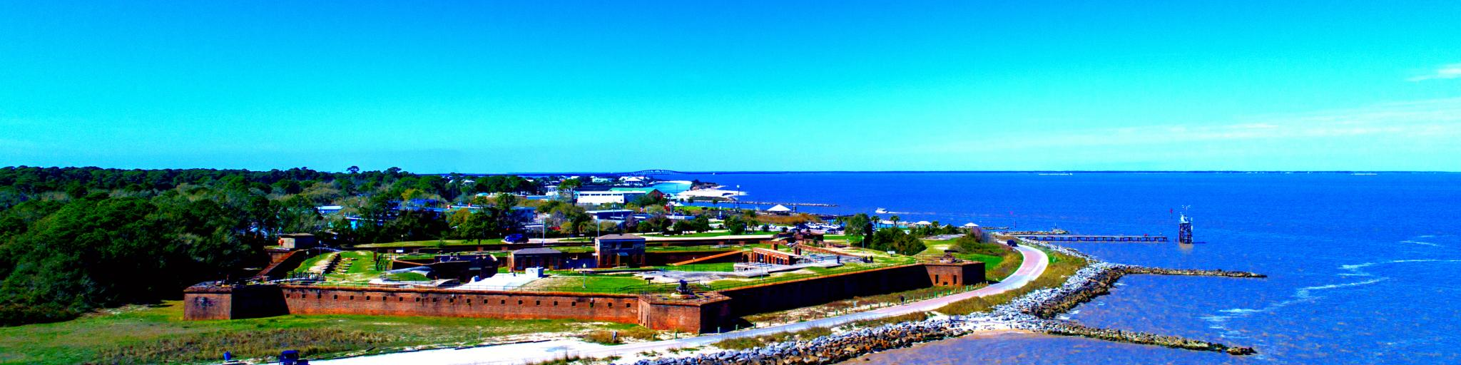 A panoramic view of a pentagon-shaped Fort Gaines along Mobile Bay in Dauphin Island, Alabama, USA, in fair weather