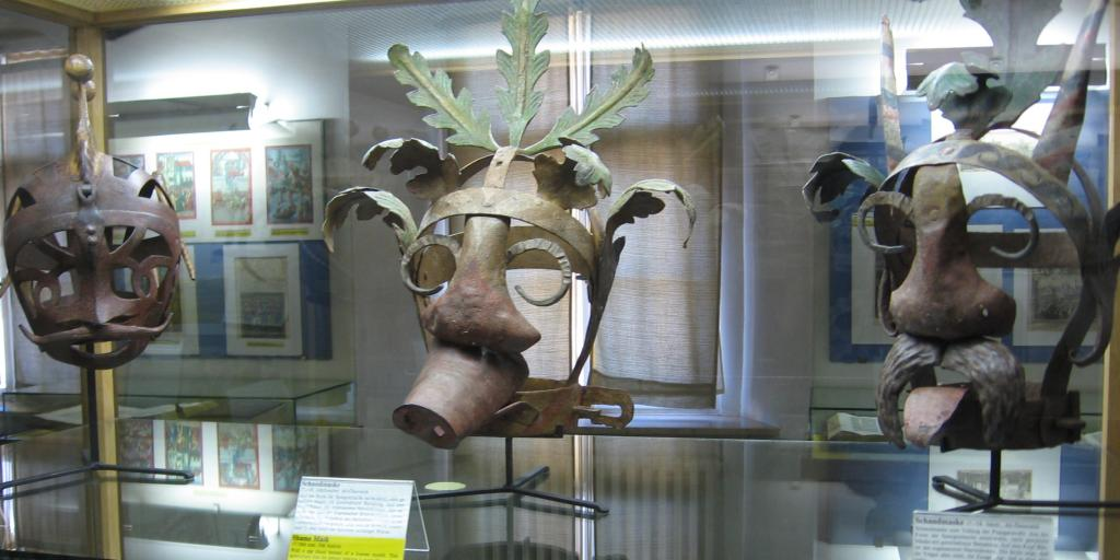 Three iron shame masks at the Medieval crime museum, Rothenberg; one has a pig snout, another a tongue hanging out