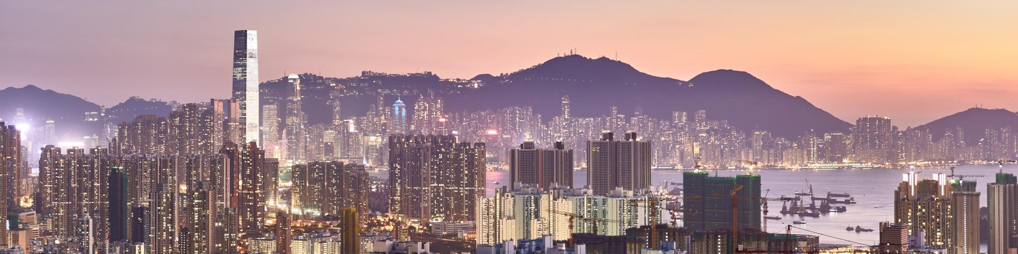 The Hong Kong skyline lit up amid a pink sunset with the harbour in the middle and mountains in the background