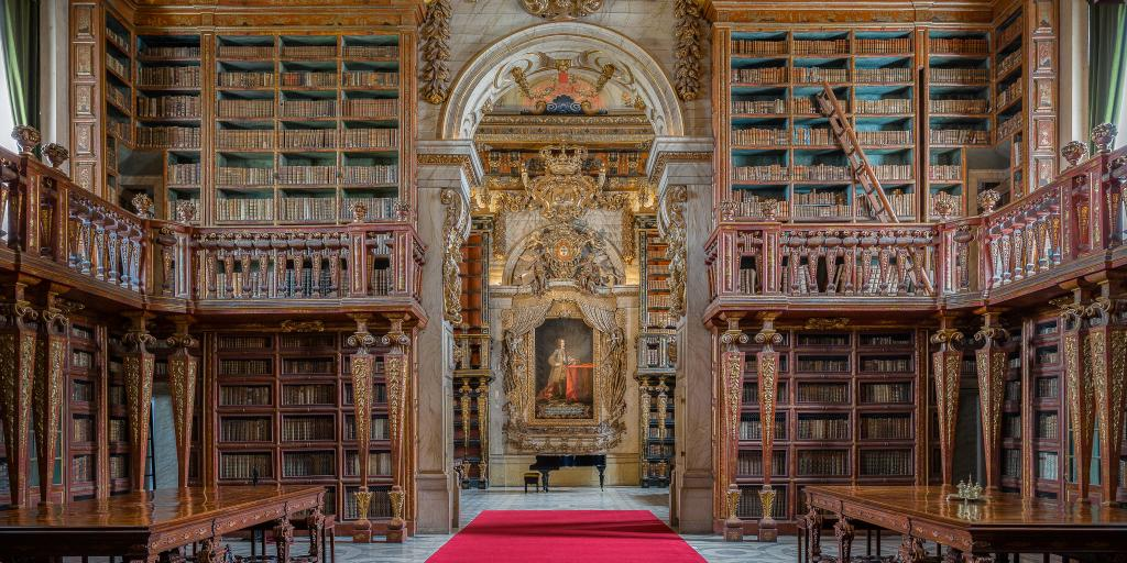 A red carpeted floor and ornate bookcases in Biblioteca Joanina, Coimbra