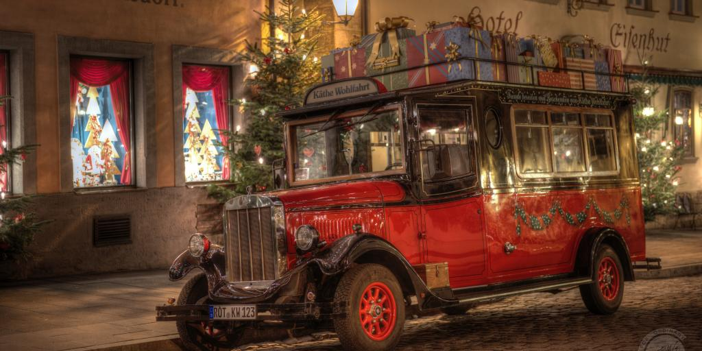 The red Kathe Wohlfahrt Bus piled with presents on the top, sitting outside the German Christmas Museum at night, surrounded by fairy lights and Christmas trees