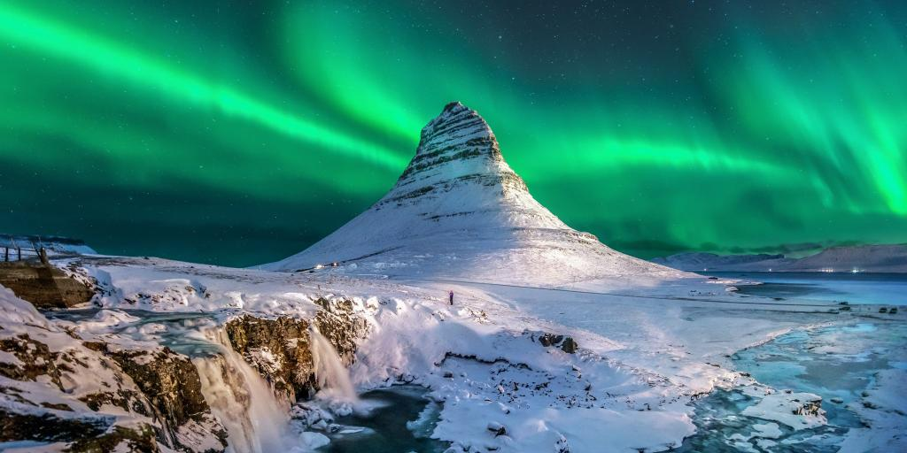 Green Northern lights in the sky over Iceland, with a snow capped mountain and waterfalls below it