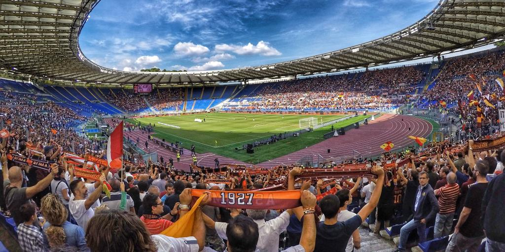 A view of the pitch taken from the stands of the Stadio Olimpico, with the crowd holding up AS Roma scarves