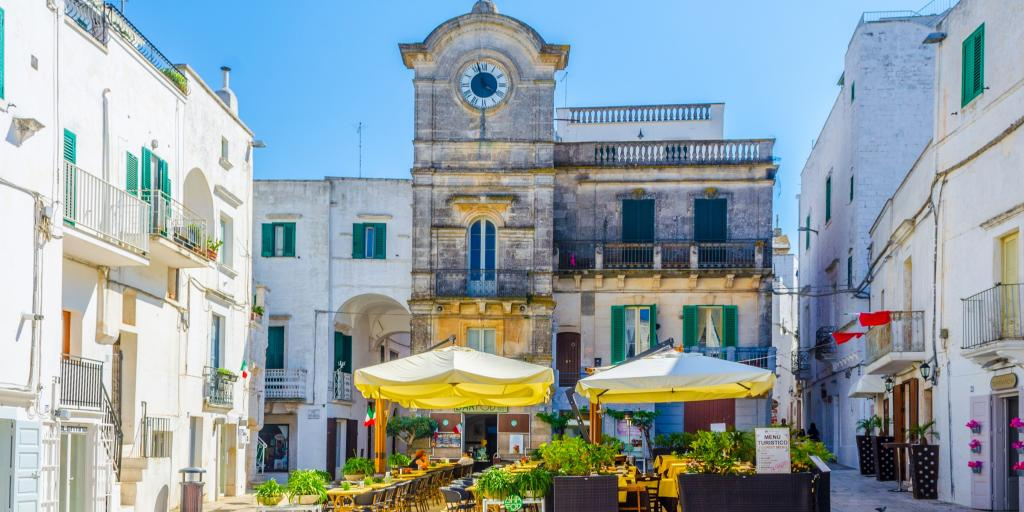 Cisternino clock tower with a cafe in front against a blue sky