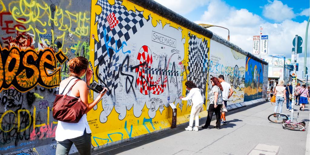 People look at the artwork painted onto the East Side Gallery section of the Berlin Wall