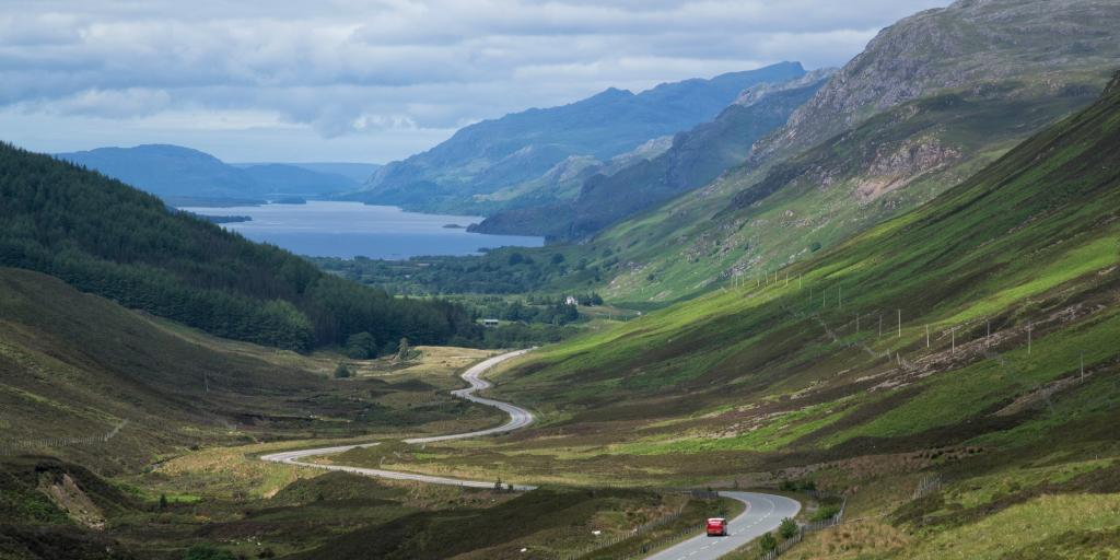 A red car driving down a winding road between two mountains, with a loch in the background