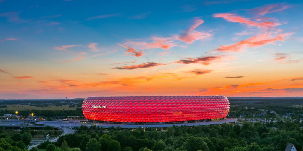 The bubbled exterior of the Allianz Arena lit up red with an orange sunset as a backdrop
