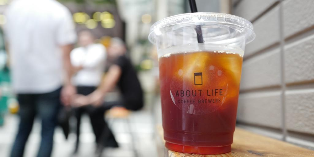 An iced coffee with the About Life Coffee Brewers logo on it