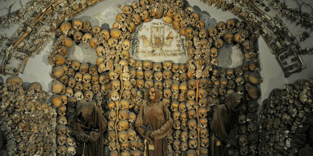 Arches on the wall of the Capuchin Crypt made out of skulls, with three mummified monks in the foreground.