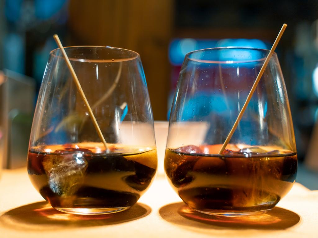 Two glasses with vermouth with a slice of orange and olives