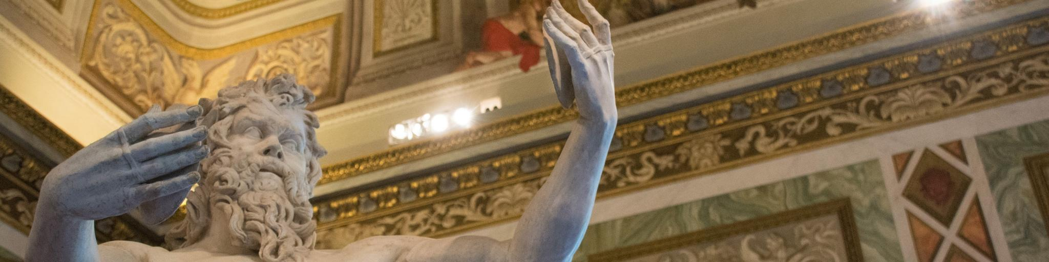 A statue at the Galleria Borghese holding his arms up, with very detailed yellow and red architecture in the background