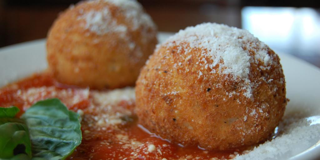 Arancini balls sitting in tomato sauce and topped with grated Parmeggiano