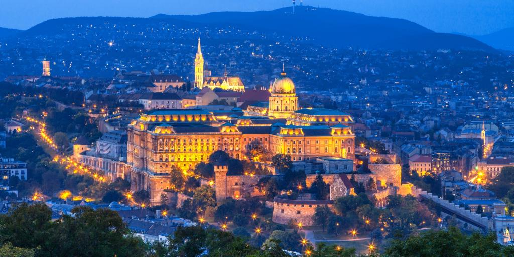 A view over the city of Budapest at dusk with the Budacastle and its dome lit up in the middle