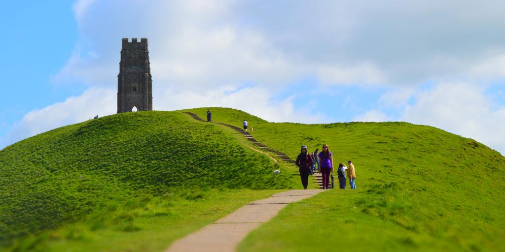 People walking down from Glastonbury Tor with the tower in the background