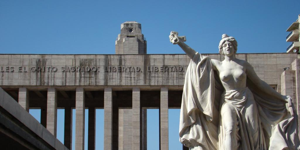 A close up of a female statue raising her arm at Monumento a la Bandera, Rosario, Argentina, with the columns of monument in the background