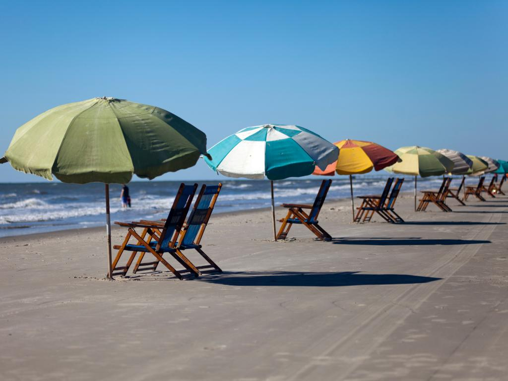 Sun chairs and colorful sun umbrellas on the beach in Galveston, Texas.