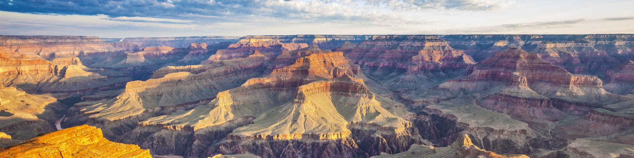 A breathtaking view of the Grand Canyon illuminated by the morning light with a cloudy sky