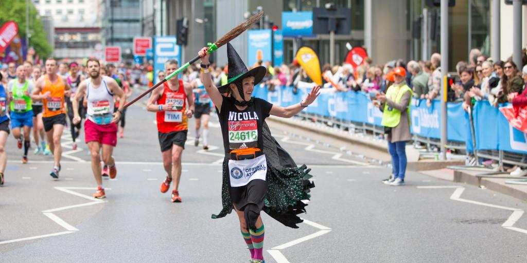 Happy Marathon runner dressed as a witch being cheered by the public