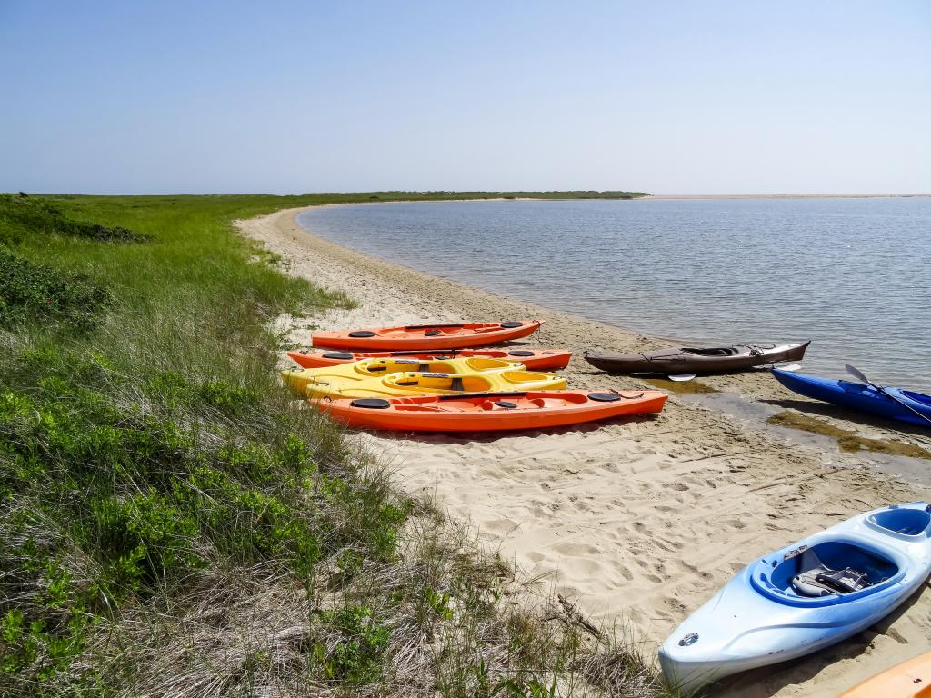 A sunny day in Tisbury Great Pond with some colorful kayaks on a white sand beach and green grass at the dunes in Martha's Vineyard in summer