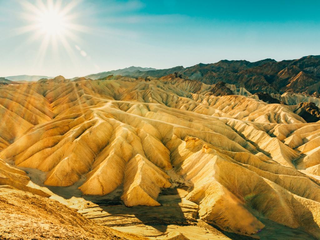 Death Valley's Zabriskie Point with unique rock and sand formations at sunrise.