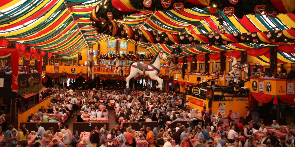 The inside of a colourful beer tent at Munich's Oktoberfest with a white horse hanging from the ceiling