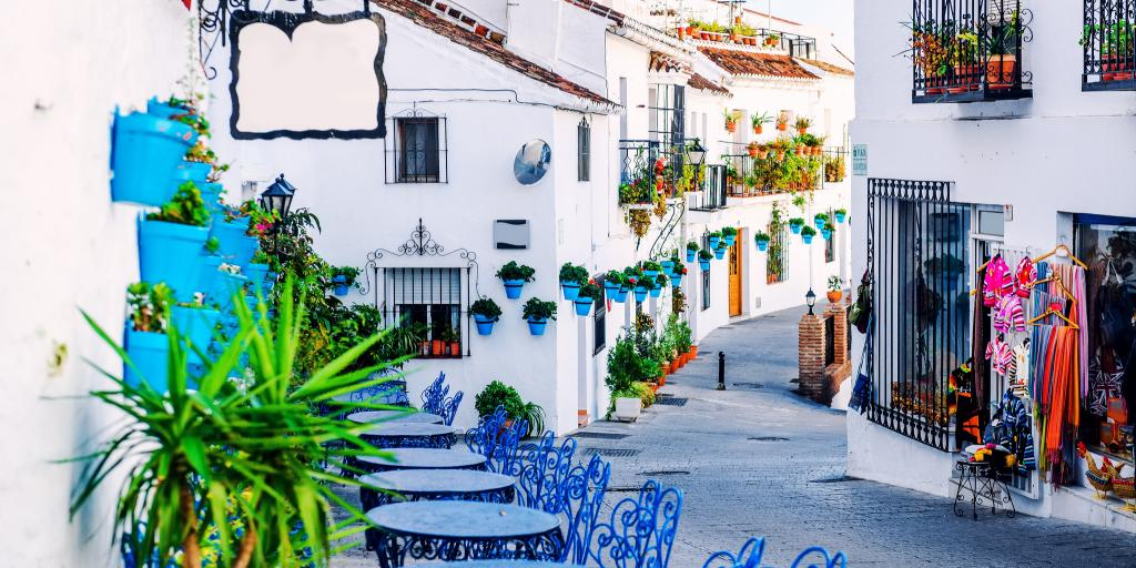 Blue tables and chairs line the charming streets of Mijas