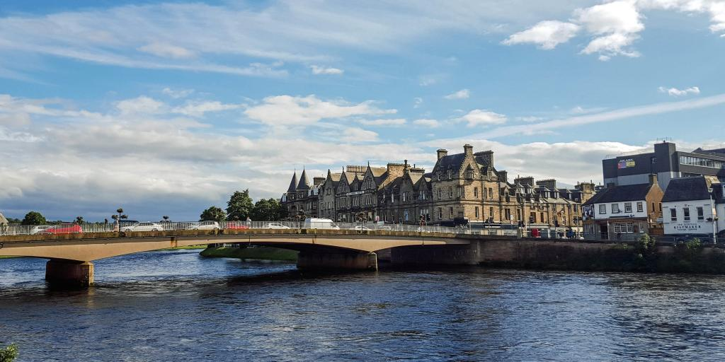 A view of the River Ness, Inverness, with Gothic style buildings on the right hand side and a traffic filled bridge going over it.
