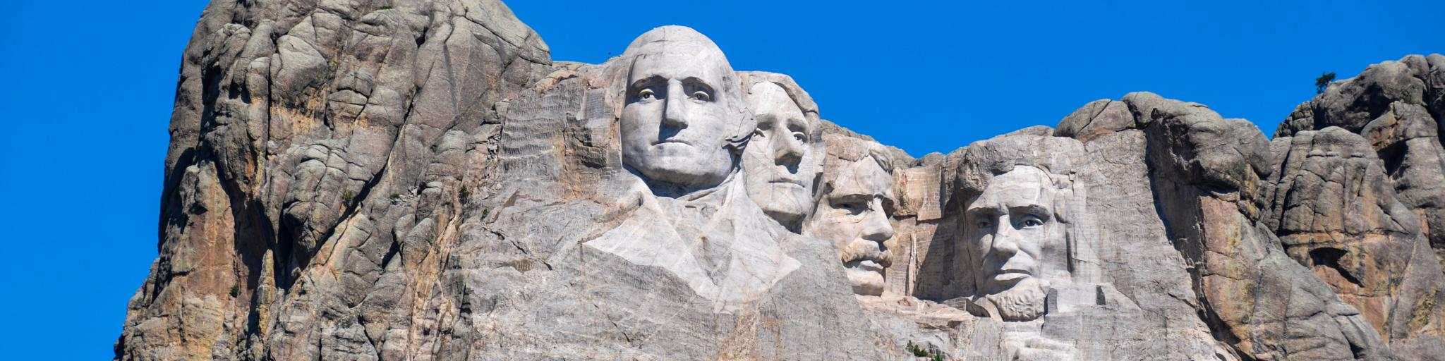 A scenic view of the 60-ft high granite sculpture of the four presidents of the United States in the Black Hills with a green forest at the foot of the mountain in a sunny morning in Mount Rushmore National Memorial Monument in South Dakota