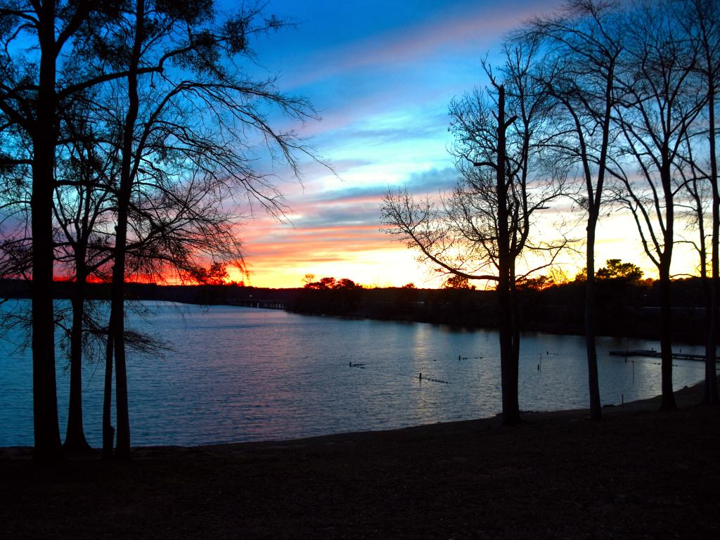 A beautiful golden orange sunset in Lake Oconee with trees surrounding the water