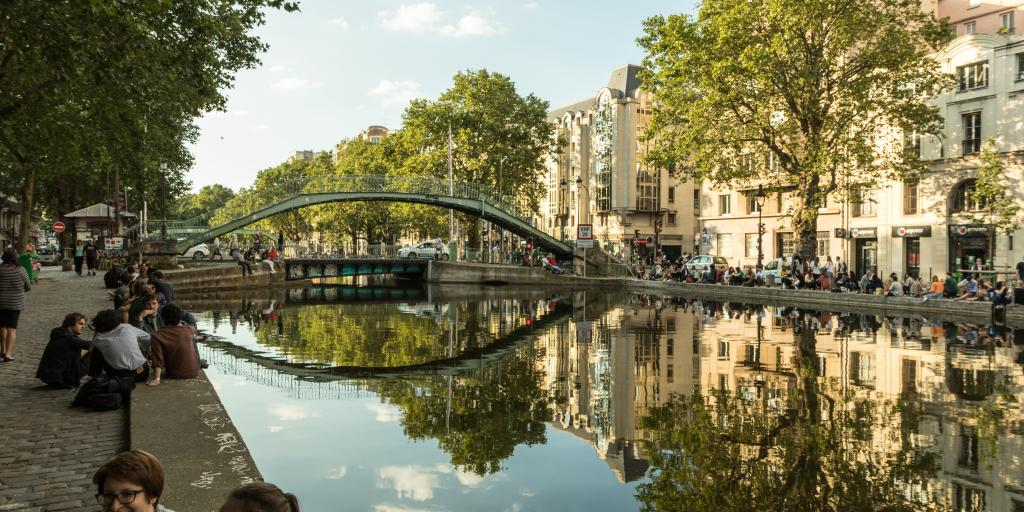 People sit and chat along the banks of Canal Saint-Martin in Paris