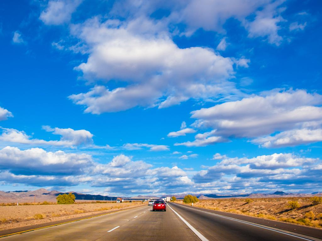 A busy road of Interstate 15 with cars in the road in a blue, cloudy, sunny weather