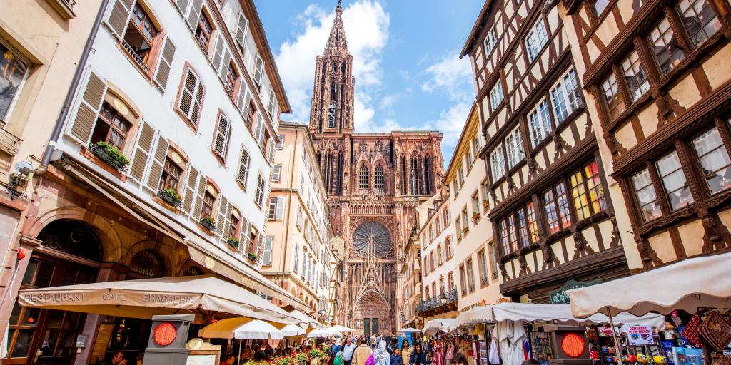 View of a crowded street with old buildings either side and the Notre-Dame cathedral at the end of it, in Strasbourg, France