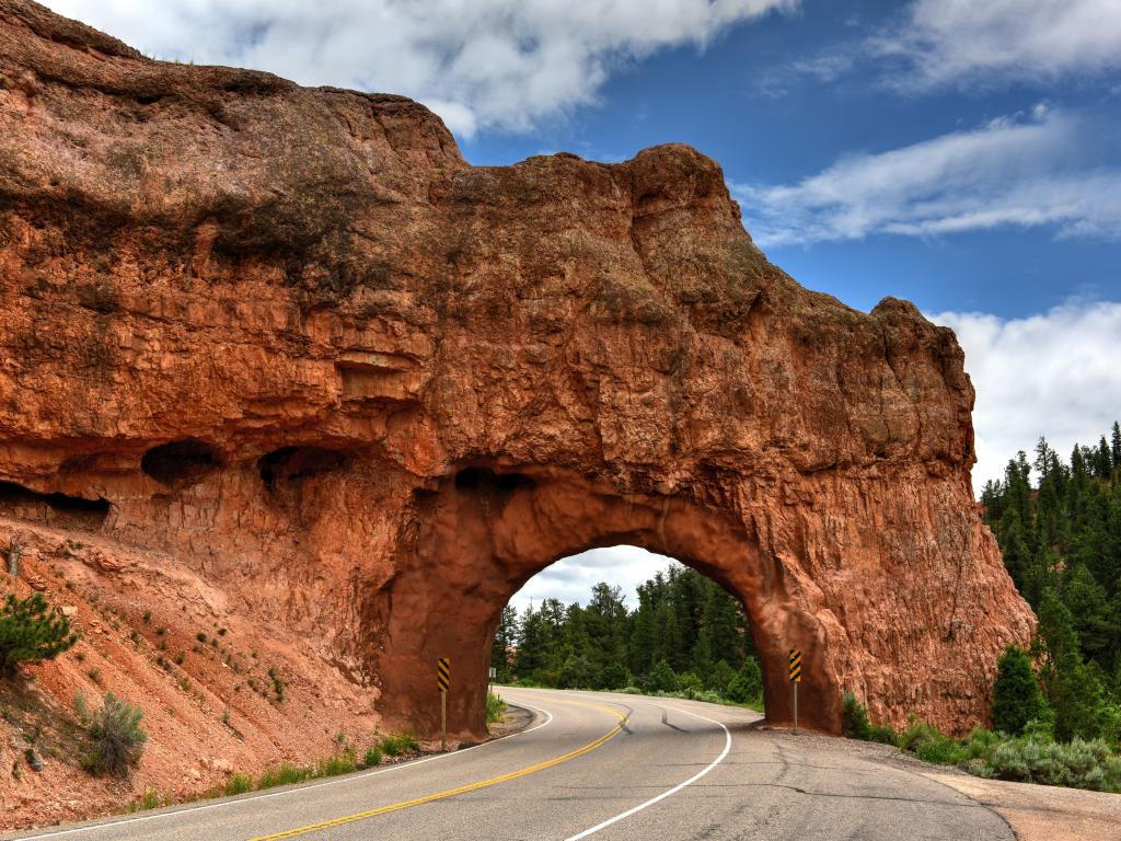 A natural red stone arch formation in the highway in Bryce Canyon National Park on a sunny morning