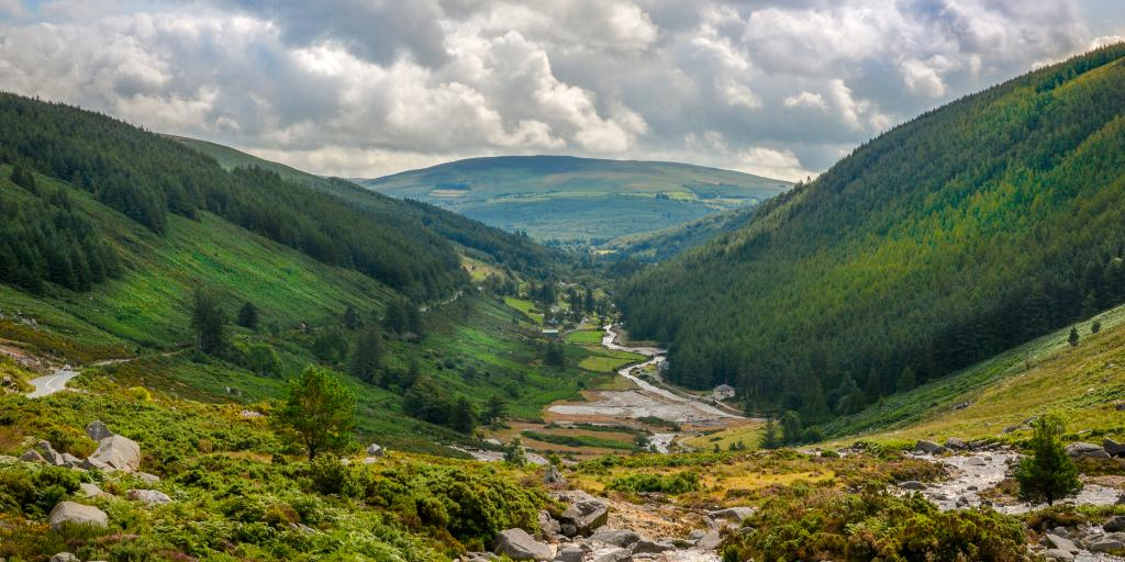 A river cuts through the lush green Glendalough Valley in County Wicklow, Ireland