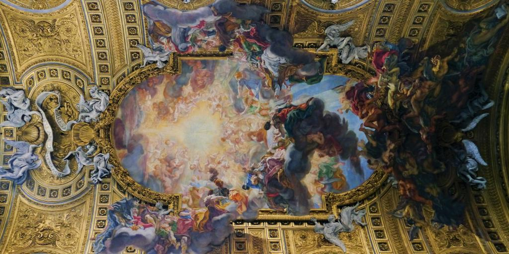 The ceiling fresco at Chiesa del Gesù, with a gold barrel shape and angels appearing to descend from the ceiling