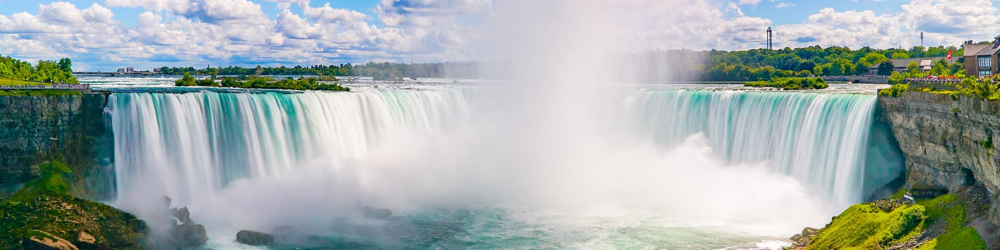A panoramic view of the horseshoe-shaped falls with turquoise water the stunning Niagara Falls framed with green grasses and trees at summer in a blue sky with cotton-like clouds.