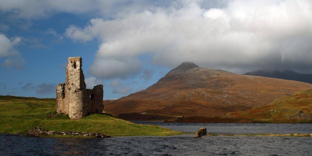 The ruins of Ardvreck Castle in Scotland with Loch Assynt surrounding it and a fiery mountain in the background