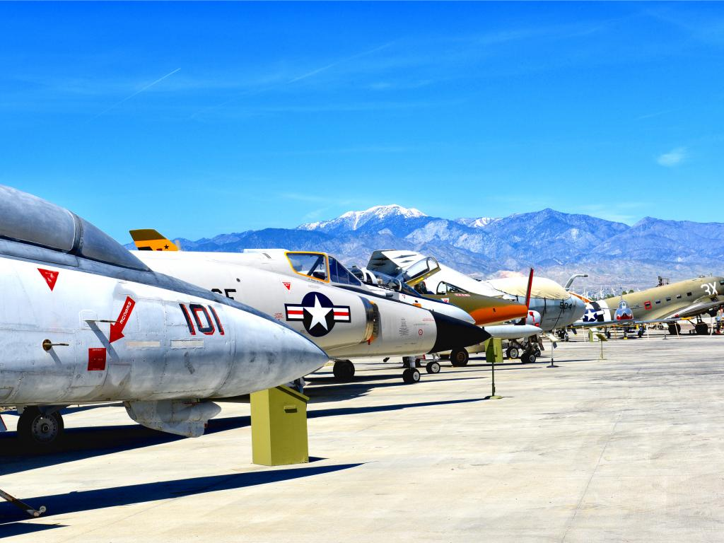 A line of vintage flyable WWII aircraft displays outside on a sunny day with a view of the mountains from afar at Palm Springs Air Museum.