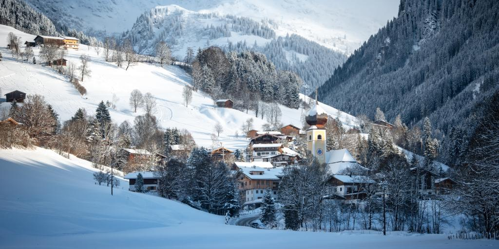 A view of the town of Kitzbühel with the church spires, pretty houses and the mountains in the background