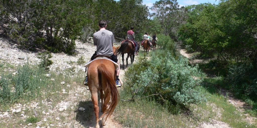 A back view of people horse riding at Silver Spur Ranch, Texas