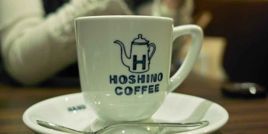 A white coffee cup branded with the Hoshino Coffee logo in Tokyo