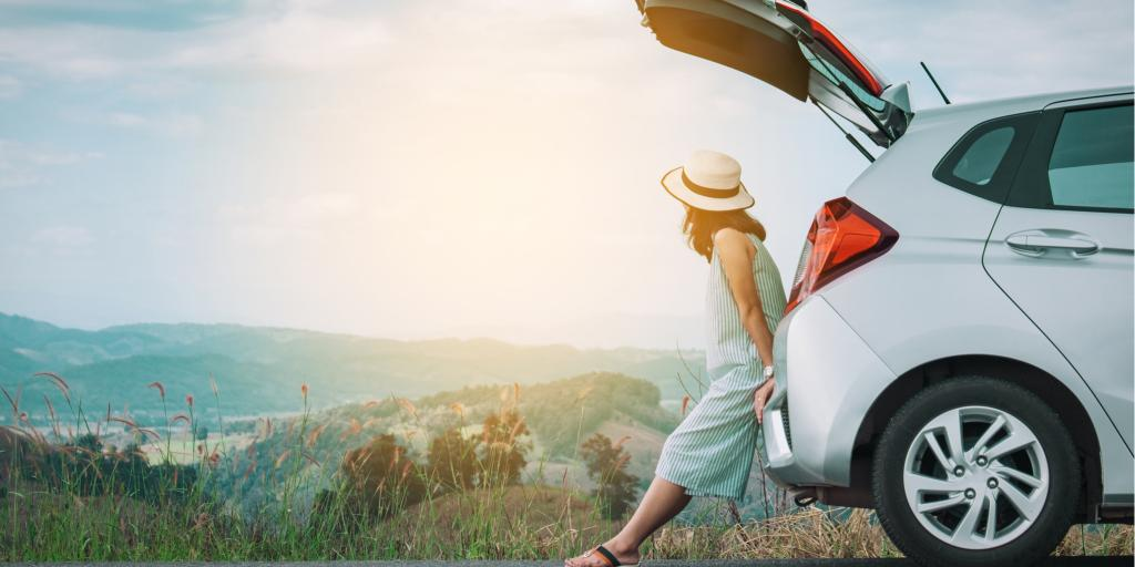 Woman traveller sitting on hatchback car with mountain scenery in the background