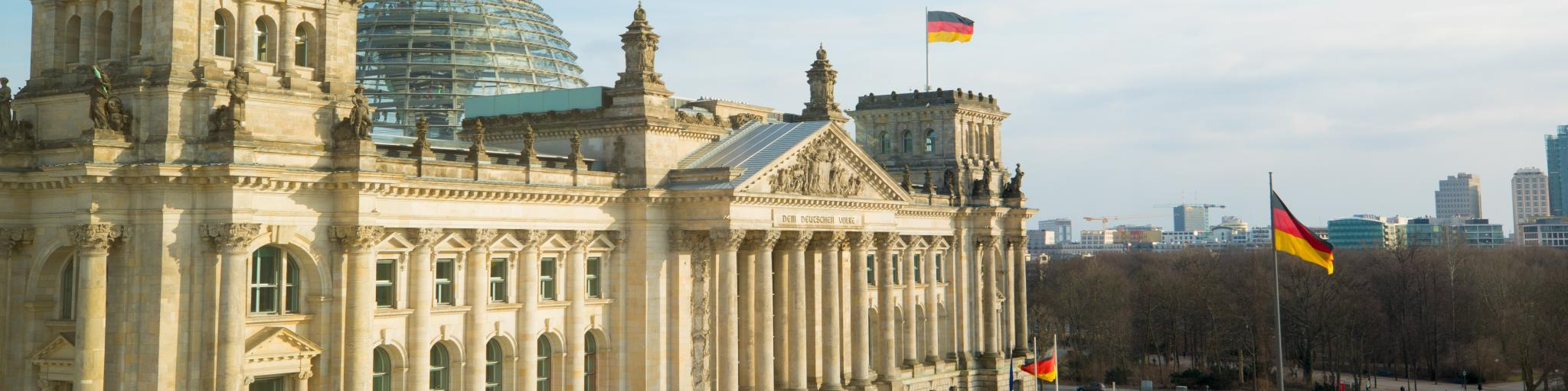 The front facade of the Bundestag building, with German flags in front of it