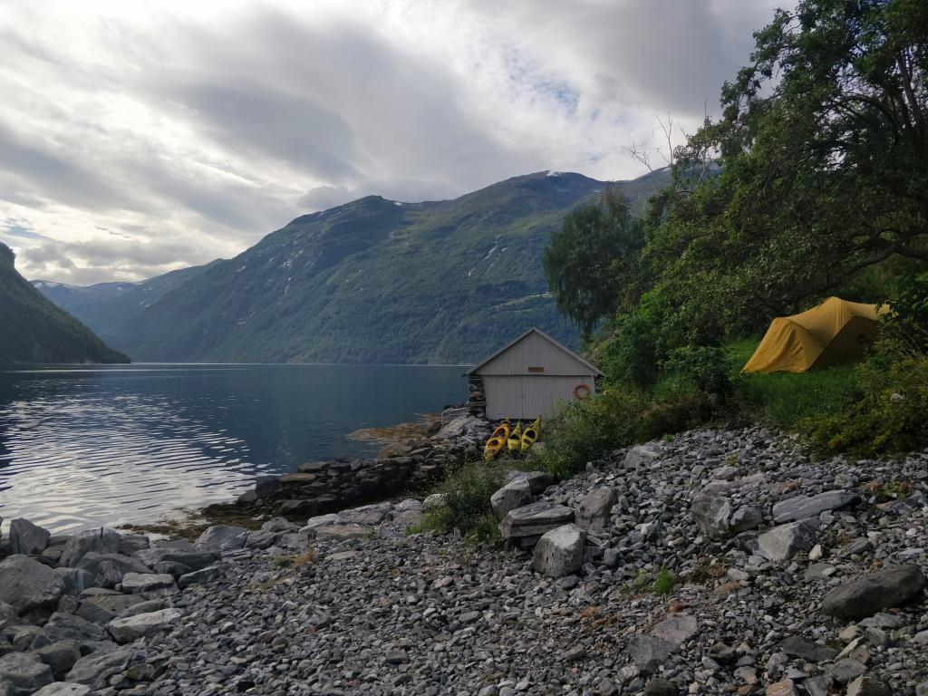A yellow tent perches on a hill in a Norwegian fjord