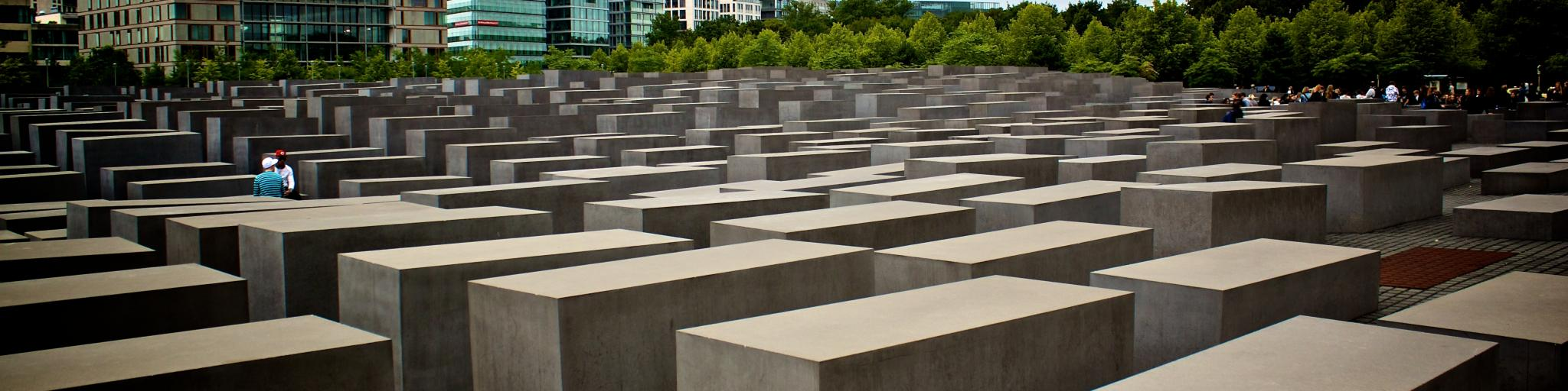 Tourists walk around the concrete blocks that are lined up like coffins at the Holocaust Memorial in Berlin