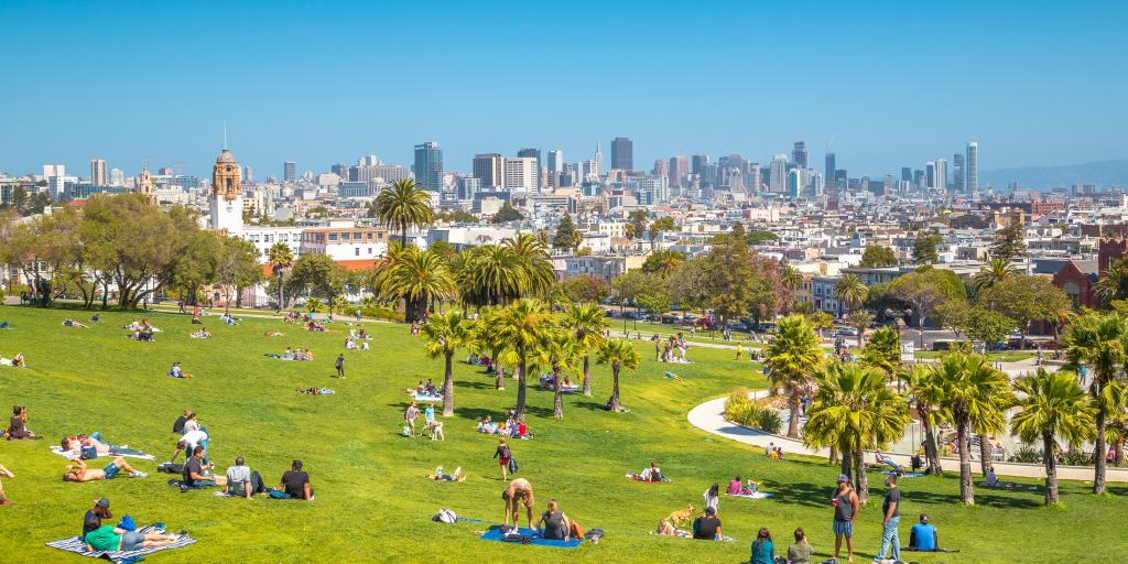 View of San Francisco from Mission Dolores Park with people relaxing
