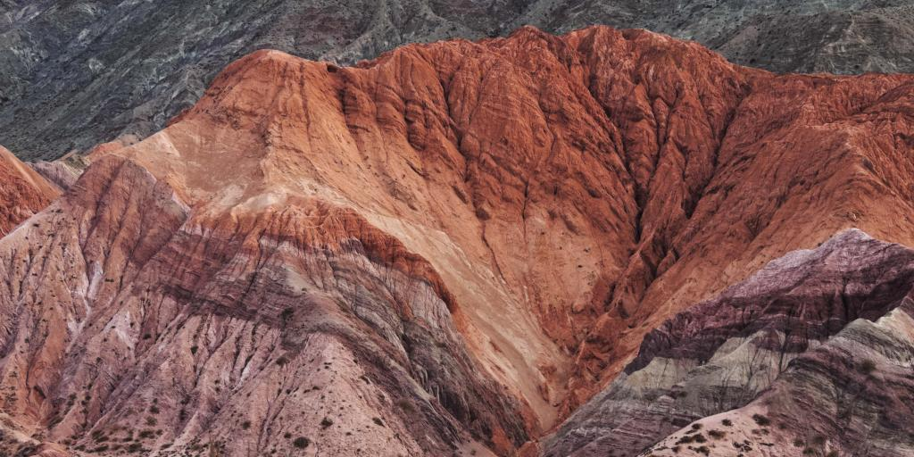 Elevated view of the Hill of Seven Colours in Purmamarca, Argentina, with different shades of reds and purples.