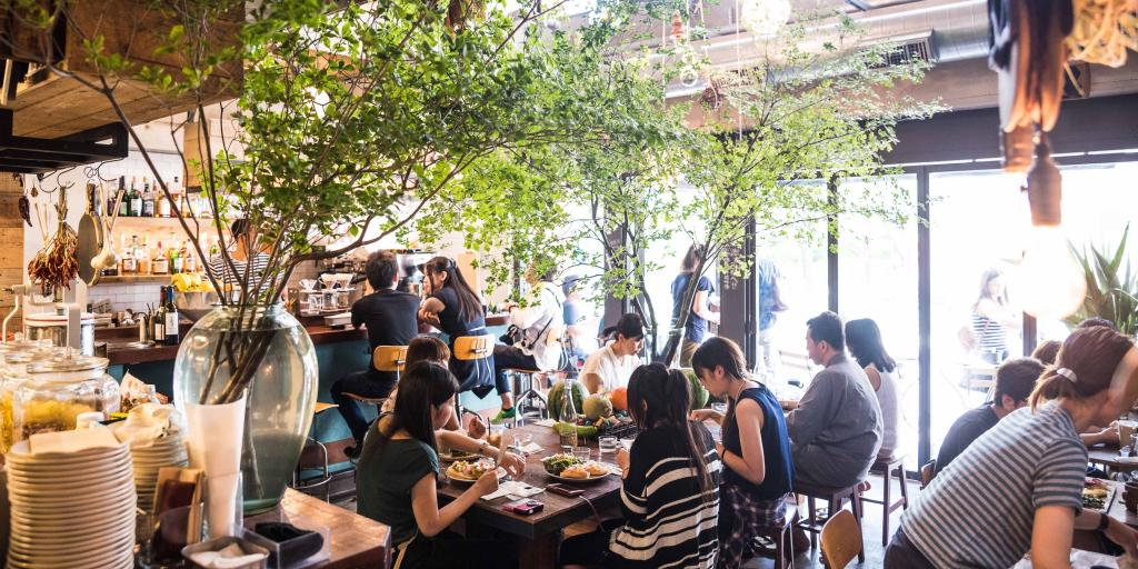 People eating brunch beneath the greenery at SUKE6 Diner in Tokyo, Japan