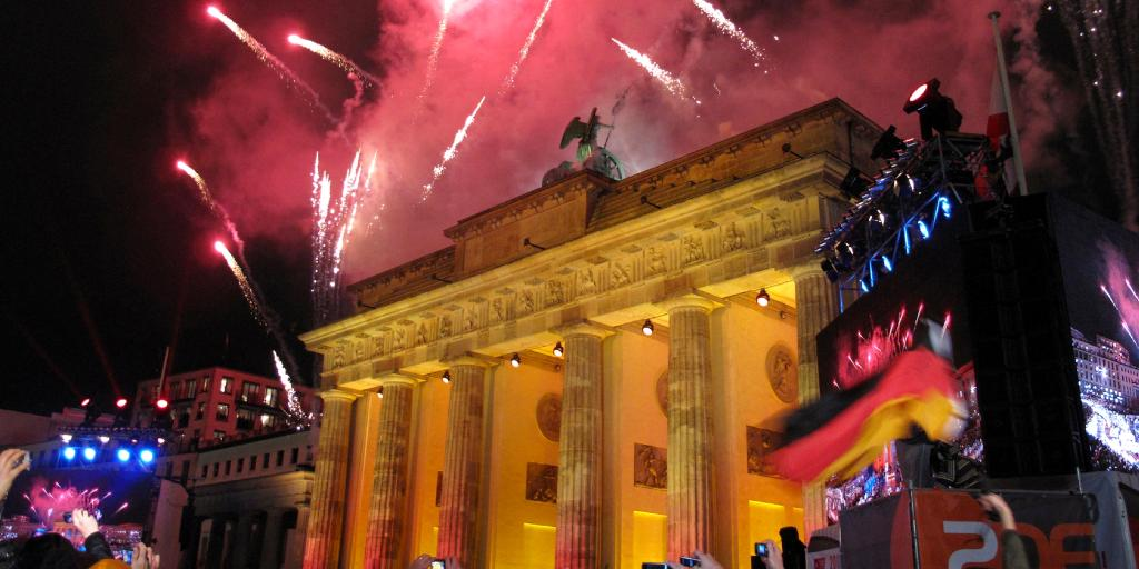 Pink fireworks exploding over the Brandenburg Gate in Berlin with a German flag to the side and people taking photos below
