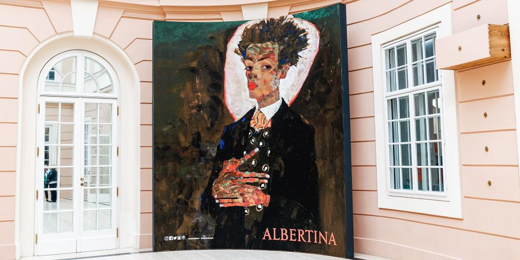 A painting of a man in a jazzy suit looking out towards the viewer, on a pink wall at the Albertina Museum, Vienna